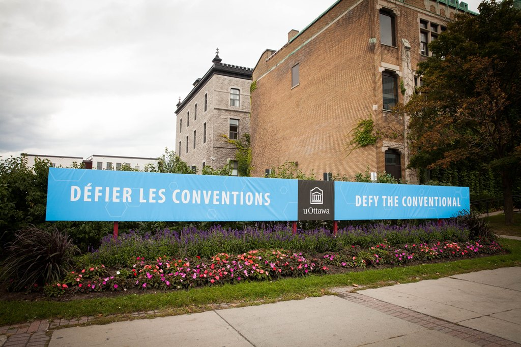 A Defy the Conventional banner in a flowerbed at a University of Ottawa entrance.