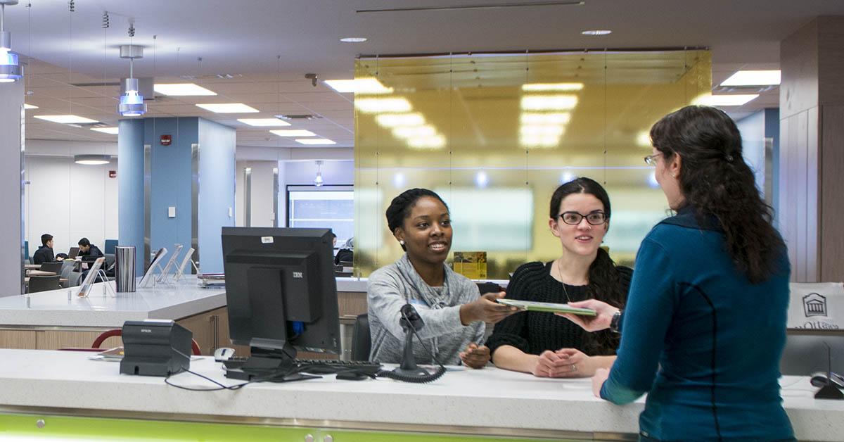 Une employée de la bibliothèque, accompagnée d'une collègue, tend un document à une étudiante qui se tient devant un comptoir.