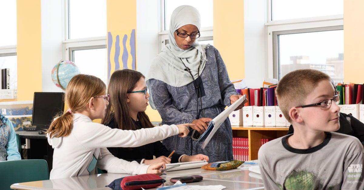 Des élèves sont assis à leur pupitre dans une salle de classe. Deux d'entre elles interagissent avec une enseignante.