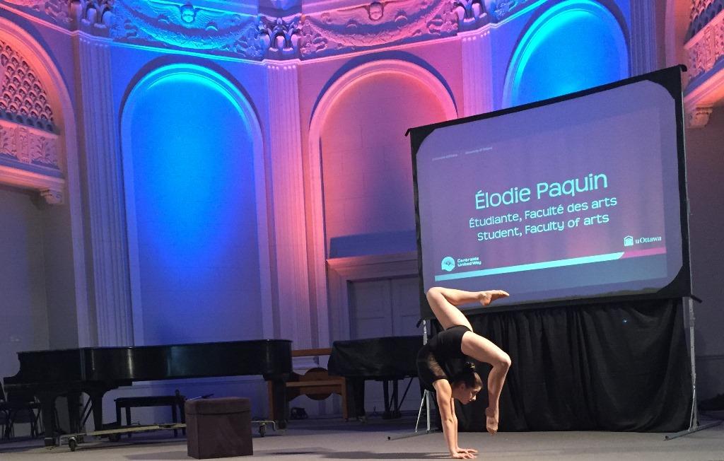 Une jeune femme sur scène dans une pose de contorsion.