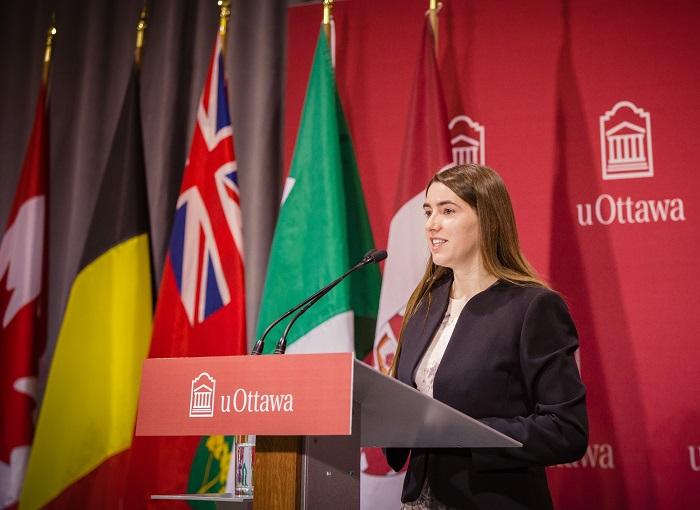 Émilie Cousineau parle au public sur le podium de la salle Huguette Labelle