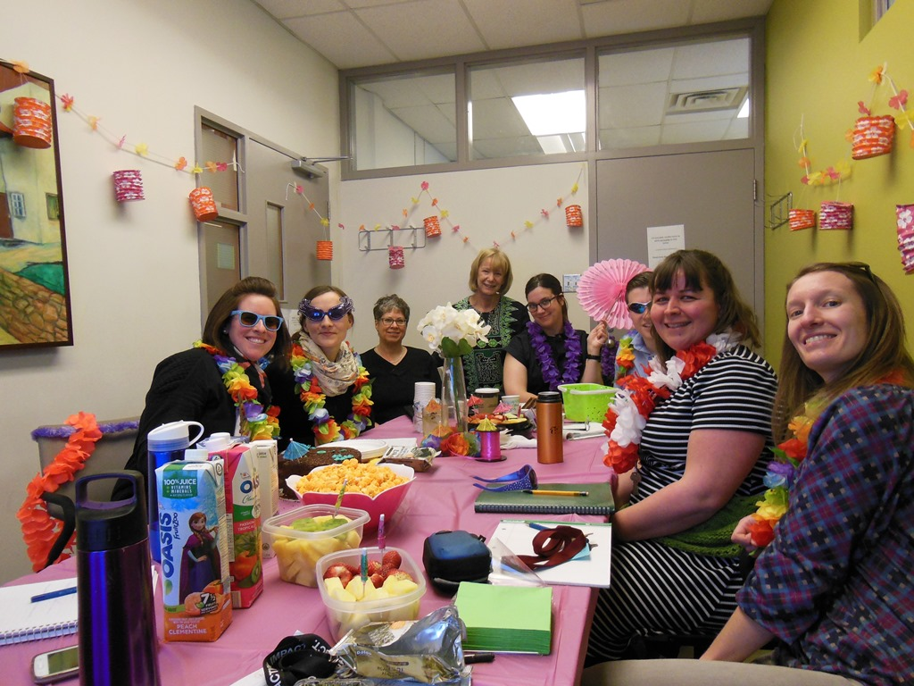 Eight women sit around a table wearing flower garlands and sunglasses.