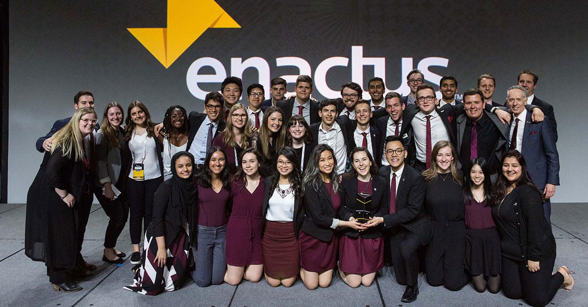 Une trentaine d'étudiants posent avec leurs conseillers scolaires tout en présentant un trophée. Au fond, on distingue le mot « Enactus » en grandes lettres, à côté d'un logo.