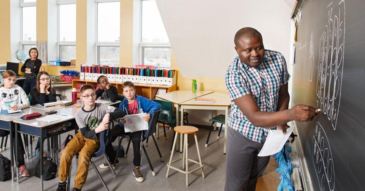Un enseignant écrit au tableau devant des enfants assis dans une salle de classe.