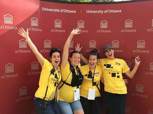 Four members of the Community life team wearing yellow t-shirts, standing in front of a uOttawa backdrop. They are waving and smiling at the camera.