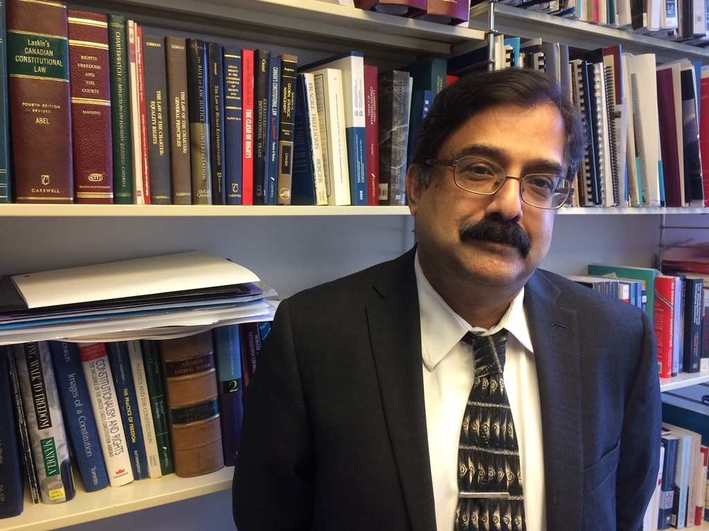 Errol Mendes smiling, in front of a bookcase.