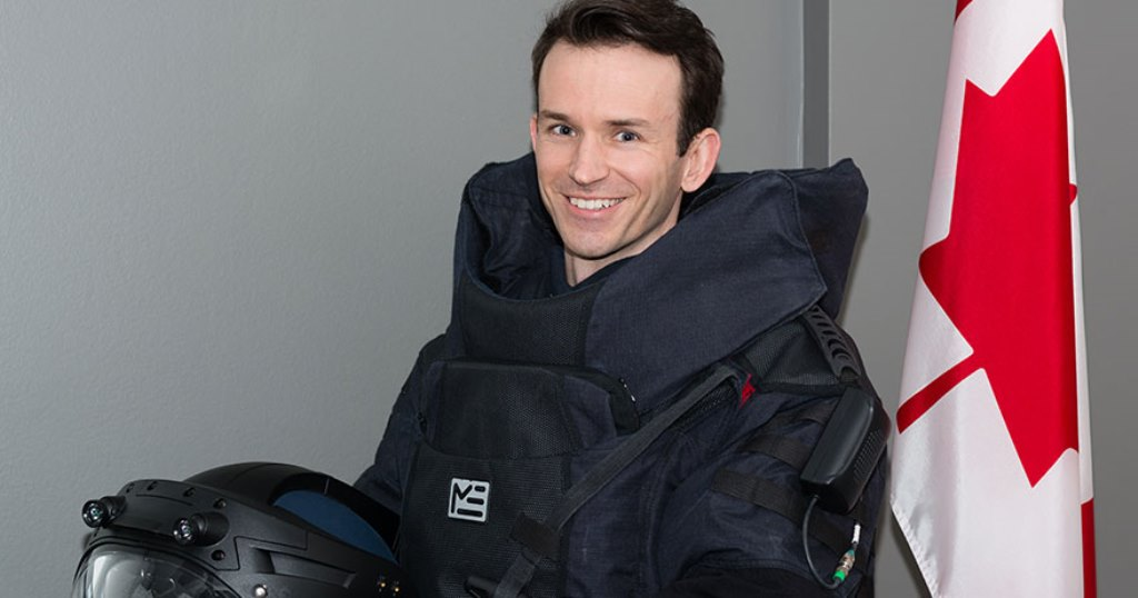 Marc Evans smiling and standing beside a Canadian flag, wearing a heavy protection-type suit and holding a helmet in front of him