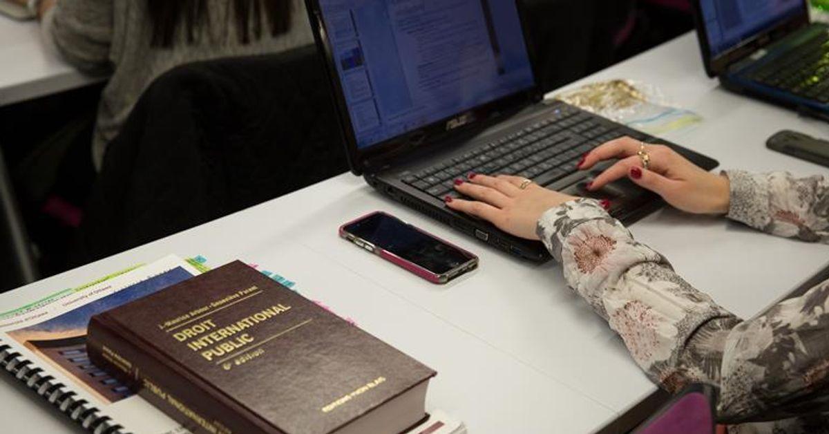 Les mains d'une femme sur le clavier d'un ordinateur portable. Un livre de droit est posé sur la table.