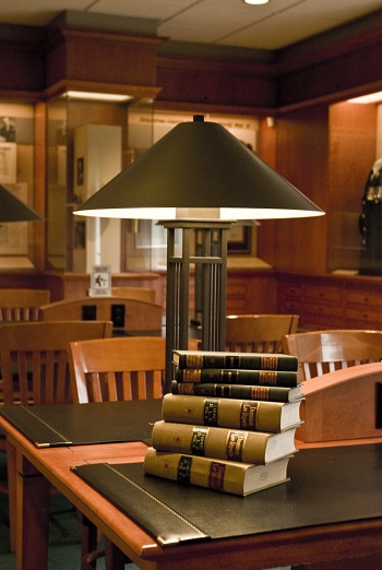 A stack of books under a lamp.