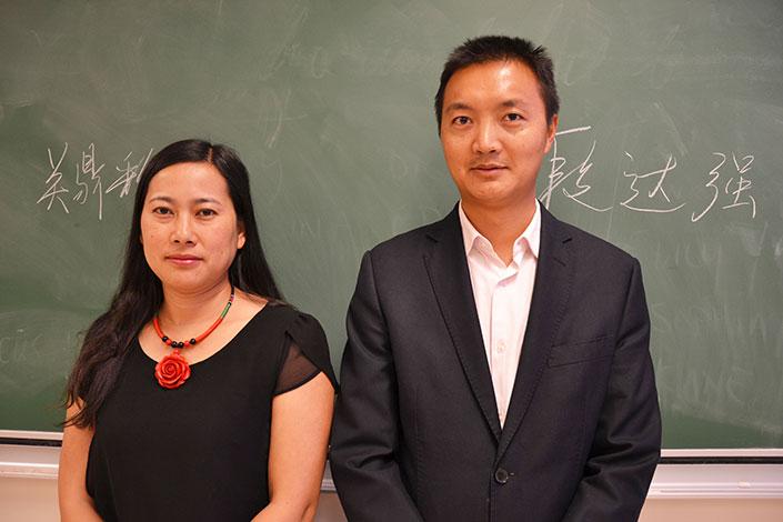 Jack et Julia côte à côte devant un tableau sur lequel est inscrit leur nom en caractères chinois.