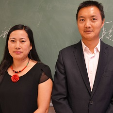 Jack and Julia stand beside each other in front of a blackboard displaying their names written in Chinese.