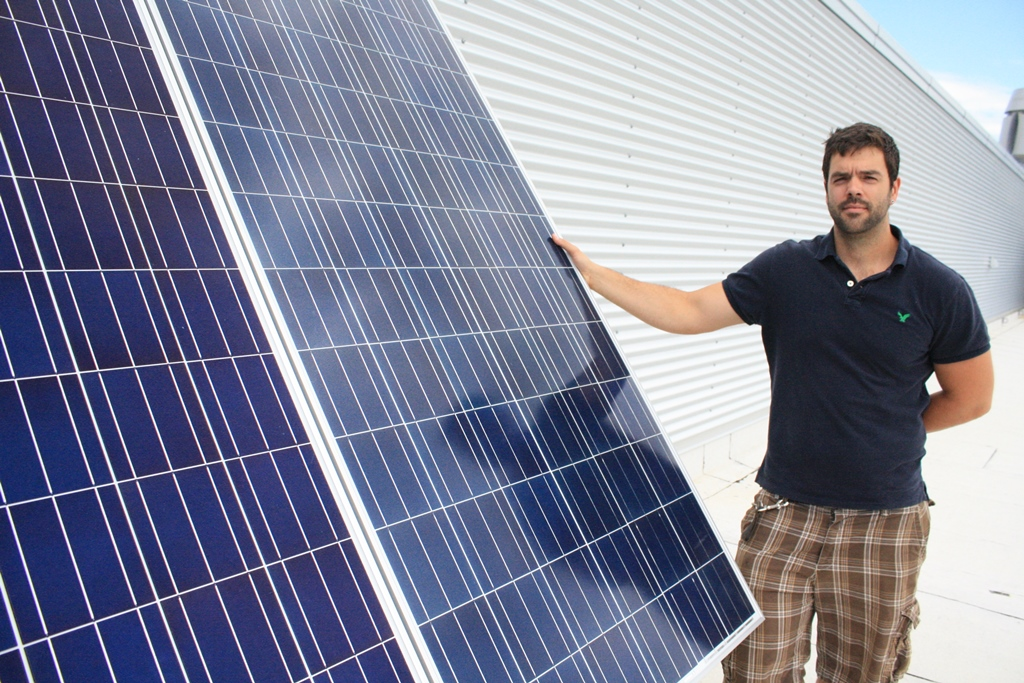 Jonathan Chiasson poses with his hand on solar panels.