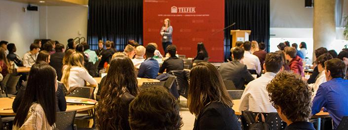 Assis et vus de dos, de jeunes gens écoutent une conférencière, debout au fond de la salle.