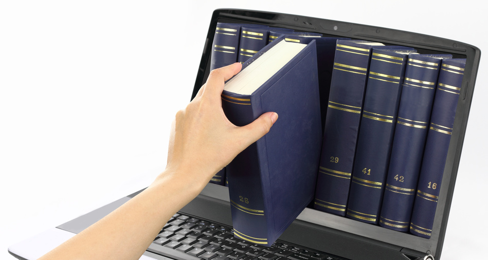 a hand is reaching for a book coming out of a computer screen.