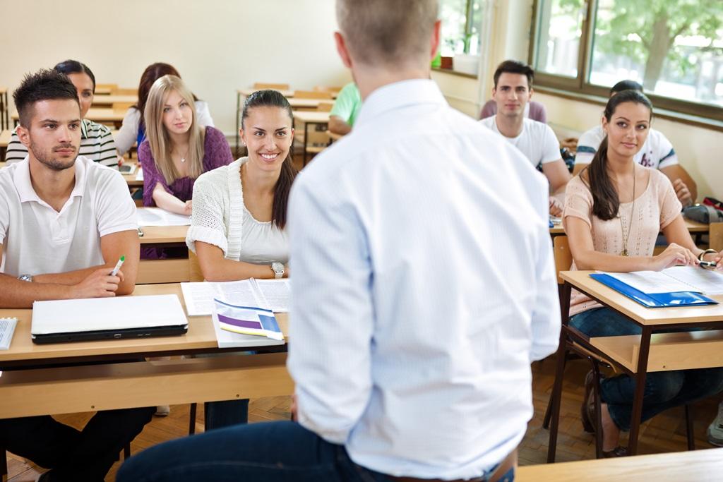 Un professeur assis en classe devant ses élèves