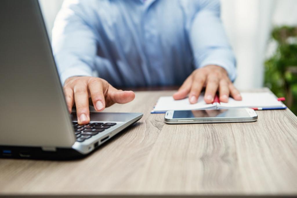 Mains masculines sur un clavier d'ordinateur portable