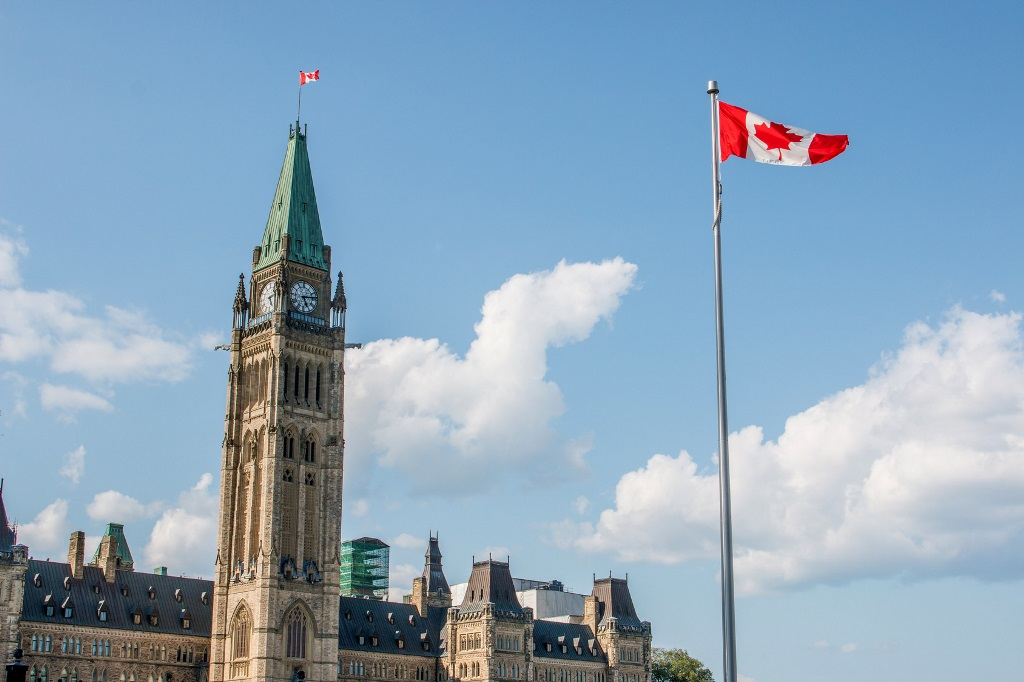 View of the Parliament. The Canadian flag is floating close by.