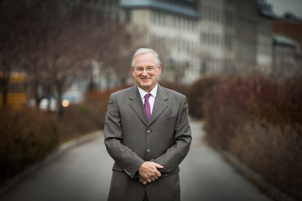 University of Ottawa president designate Jacques Frémont smiles with his hands clasped in front of him on a pathway bordered by hedges.