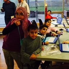 Des enfants syriens assis à une table devant des ordinateurs portables sourient à la caméra.