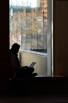 Silouhette féminine assise seule, au sol dans un couloir de l'Université.