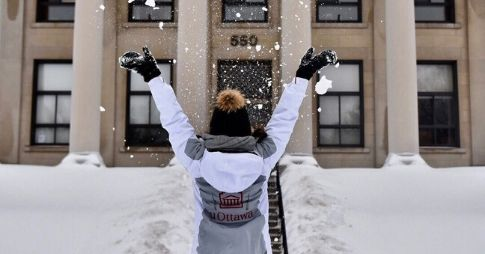 An individual wearing a jacket containing the uOttawa logo is throwing snow in the air, they have been photographed from behind.
