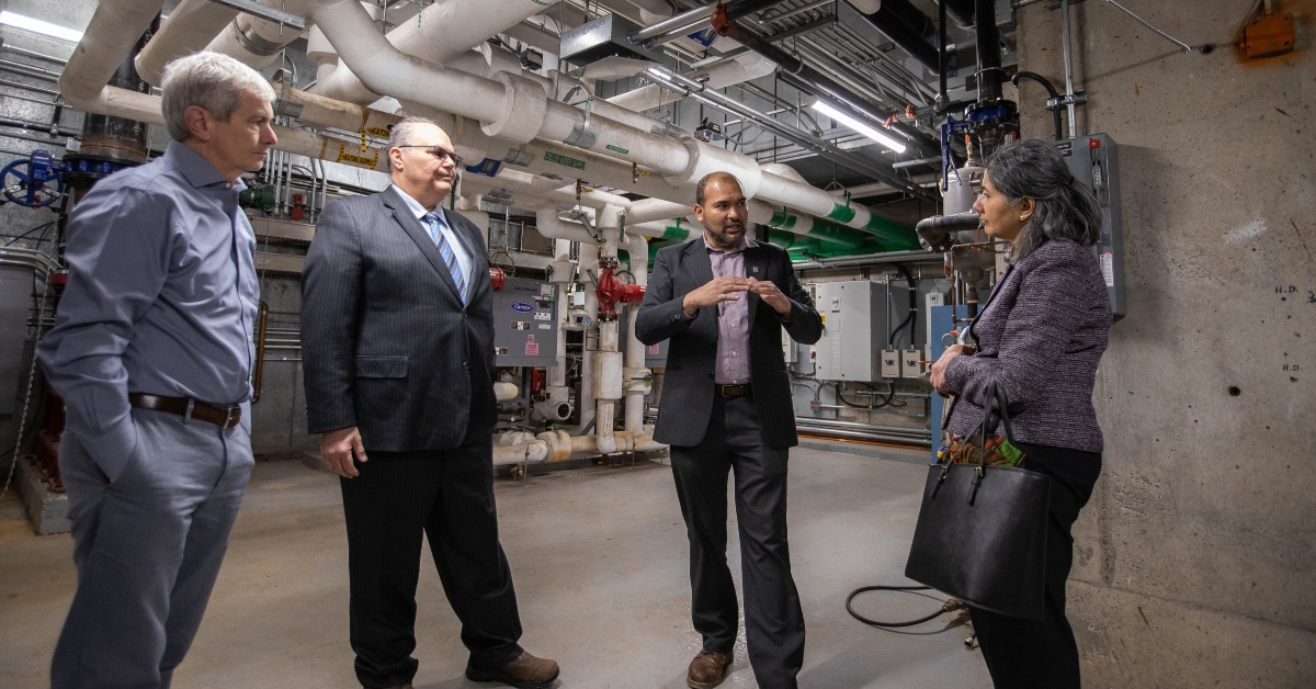 University of Ottawa Energy and Environment Manager Faizal Sudoollah talks to three Enbridge Gas executives in a mechanical room