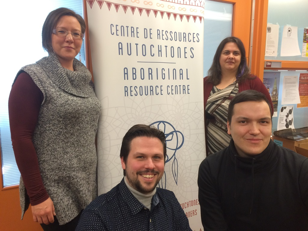 Two women and two men in front of a banner with the words Aboriginal Resource Centre on it.