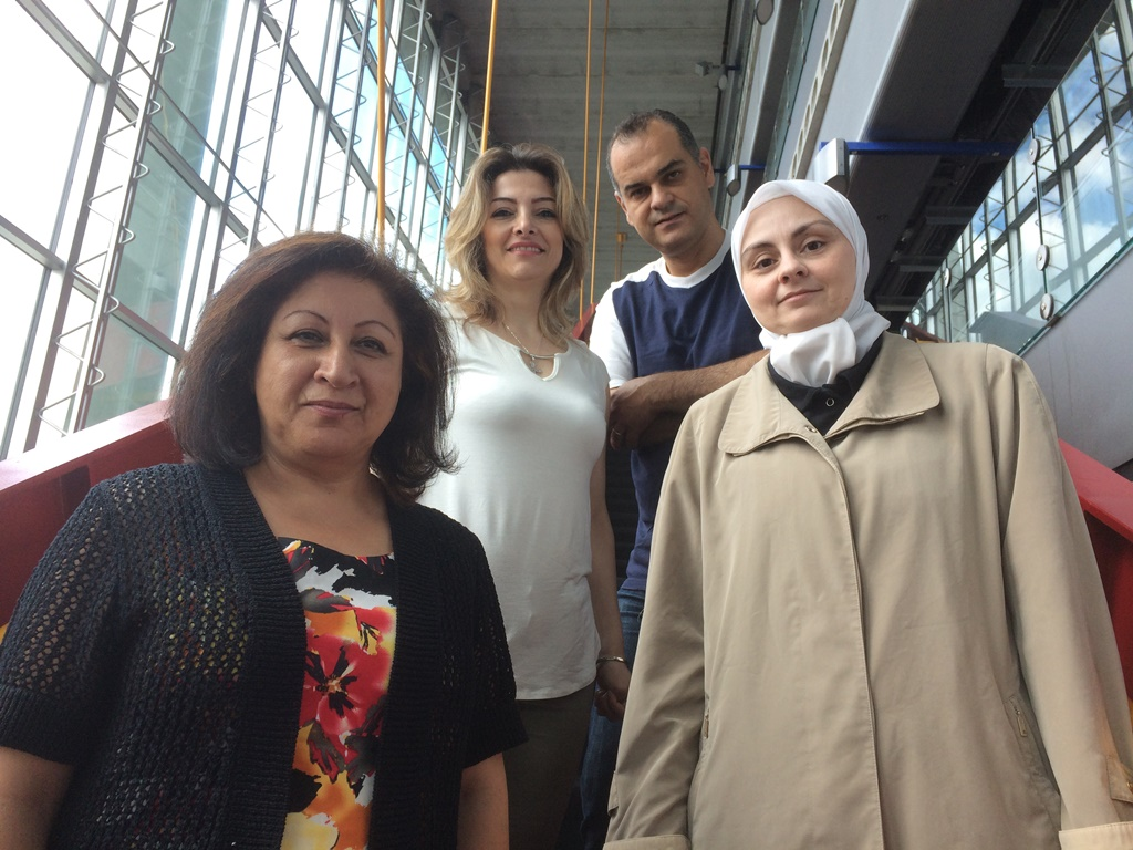 Three women and a man in front of glass doors in the entrance to the SITE building.