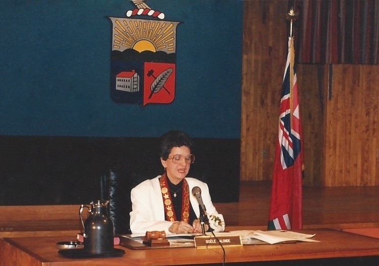 Gisèle Lalonde, surrounded by the Ontario flag and Vanier's coat of arms, sits at a table in the town hall.