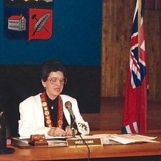 Gisèle Lalonde, entourée du drapeau de l'Ontario et des armoiries de Vanier, est assise à une table dans la salle du conseil municipal.