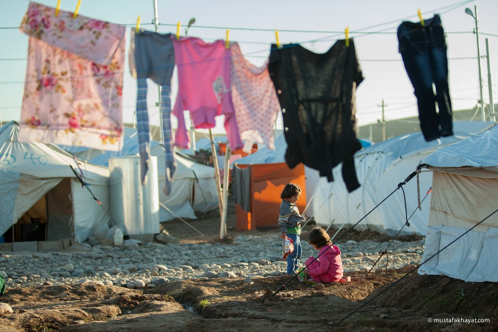 Two girls play outside on the barren, hard-packed soil of a Syrian refugee camp in northern Iraq, surrounded by densely packed tents that are home to the refugees.