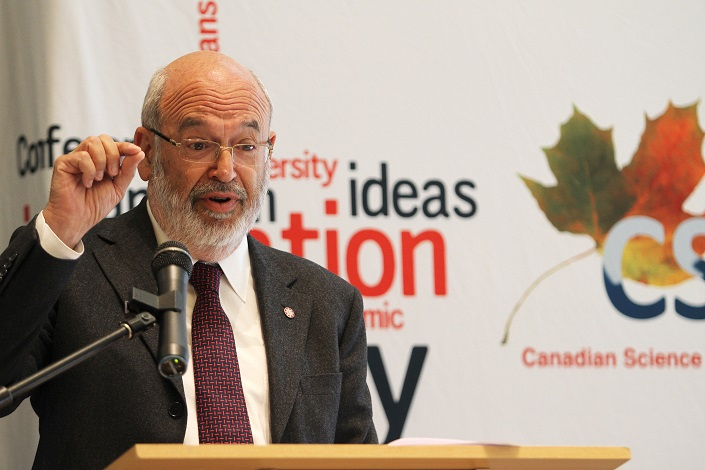 Sir Peter Gluckman speaks at a podium in front of a banner displaying words such as diversity, ideas and innovation