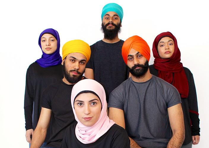 Un groupe d'hommes et de femmes portant des turbans et des hidjabs colorés.