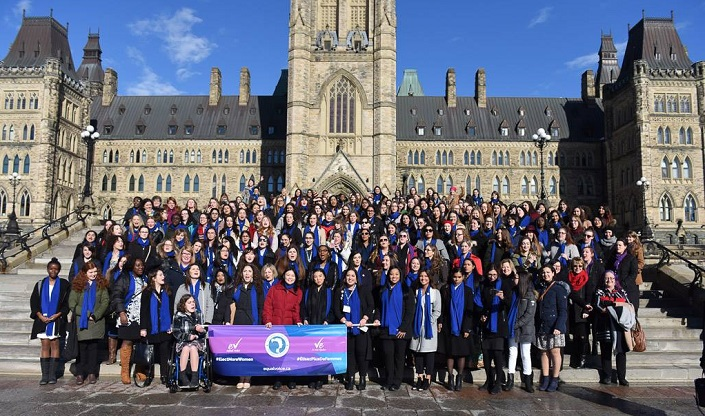 Hundreds of young women pose under the sun for a photo on the front steps of the Centre Block.