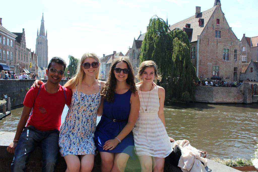One man and three women, including Chelsea Cooligan, sitting on a wall overlooking a river in Bruges, Belgium.