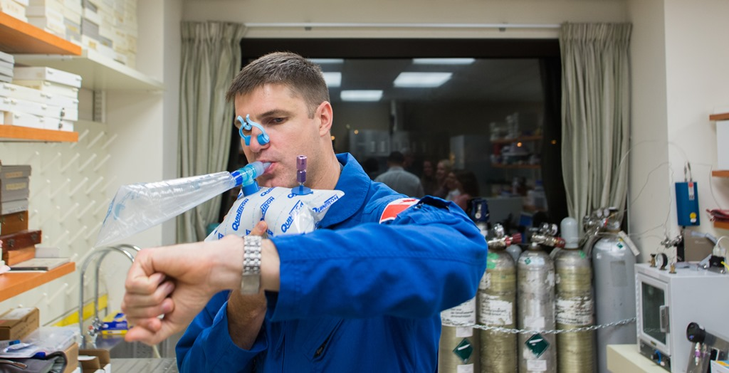 Astronaut Jeremy R. Hansen breaths into a bag wearing a nose clip.