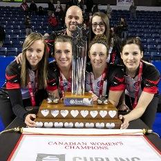 Les cinq coéquipières et l'entraîneur sourient derrière le trophée du Championnat canadien de curling féminin.