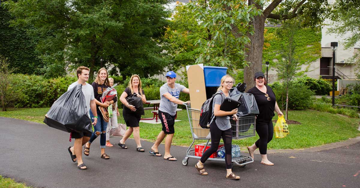 Un homme transporte des boîtes dans un panier d'épicerie, entouré d'une demi-douzaine d'autres personnes portant des sacs en souriant.