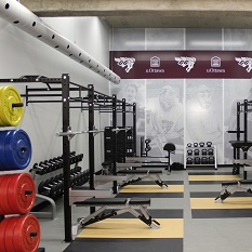 A training space that features mats on the floor and weight-lifting equipment along the walls.