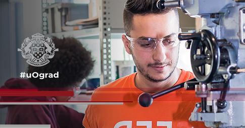 Humam utilise la presse à exercices en portant des lunettes de sécurité et un t-shirt orange