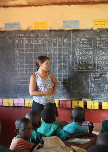 Hunter Kelly in front of a blackboard full of arithmetic problems. Several boys sit at school desks.