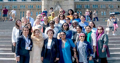 Two dozen people, mostly women, stand on the steps in front of Centre Block.