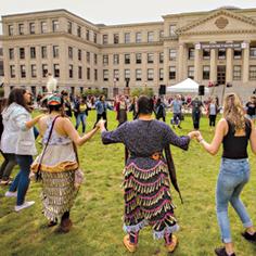 Des étudiants autochtones se tiennent la main avec d'autres étudiants de l'Université d'Ottawa dans un grand cercle sur la pelouse de Tabaret.