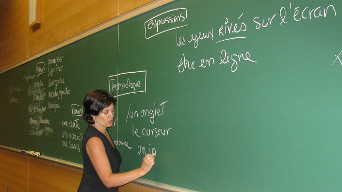 ILOB teacher at a blackboard teaching vocabulary related to new technologies.