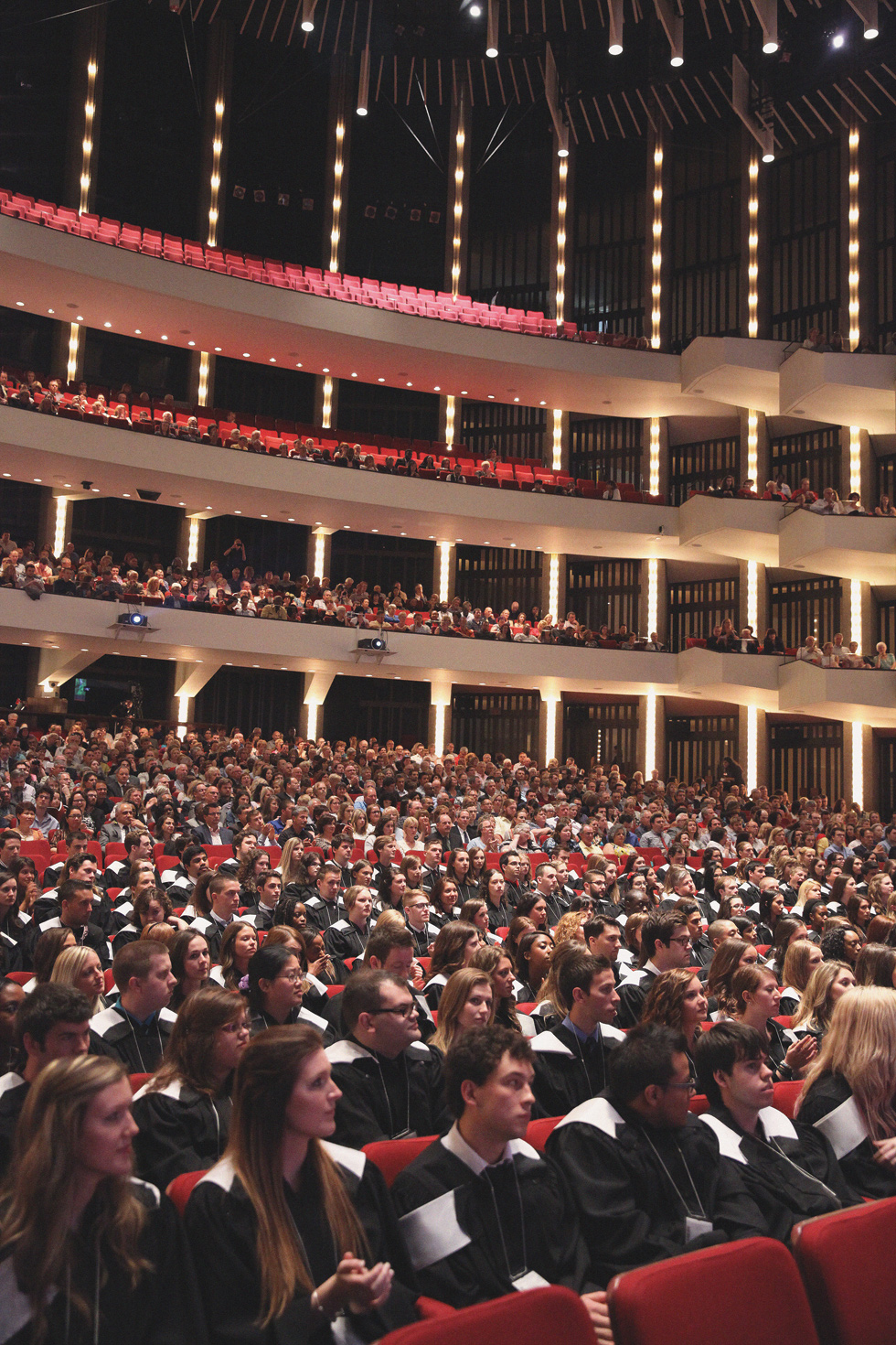 Theater full of students dressed in graduation gowns in 2013.