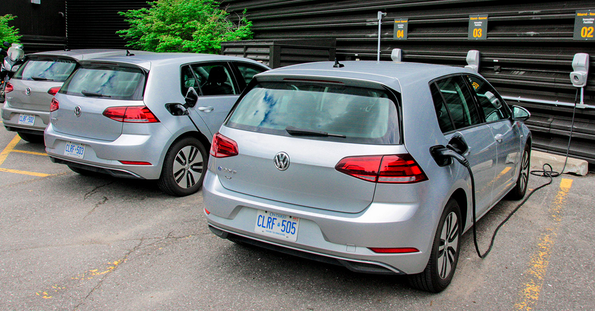 Three electric Volkswagen cars parked in a row and plugged into wall chargers