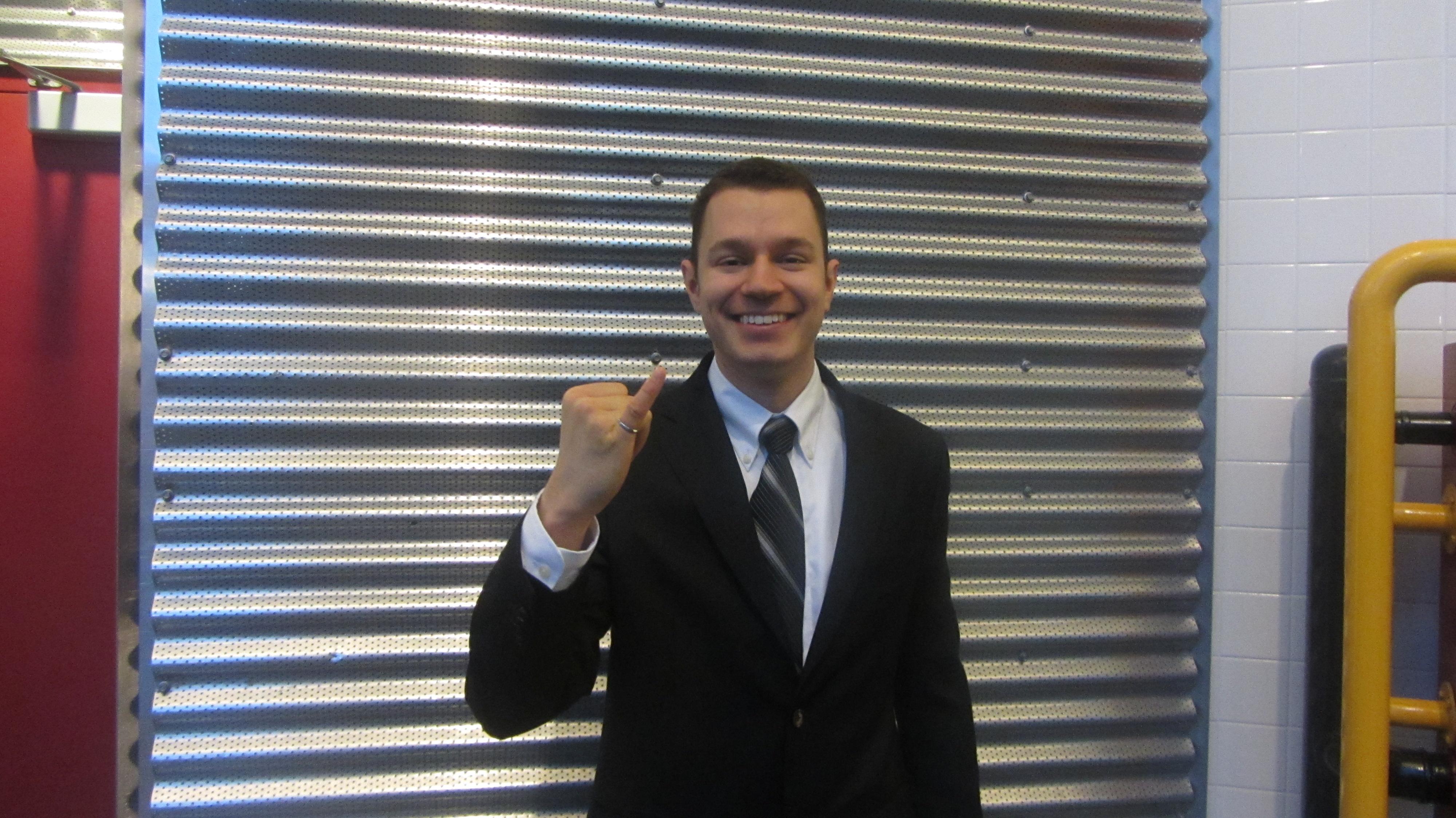 Un homme souriant vêtu d'un complet montre son petit doigt dans lequel est inséré un anneau.