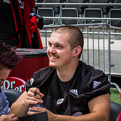 Lewis Ward sits at a table smiling signing autographs for fans.