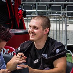 Lewis Ward assis à une table signe des autographes pour les supporteurs.