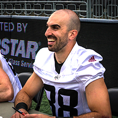 Brad Sinopoli sits at a table smiling and signing autographs for fans.